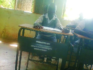 student of Oghede Community Secondary School, on one of the chair and desk donated.